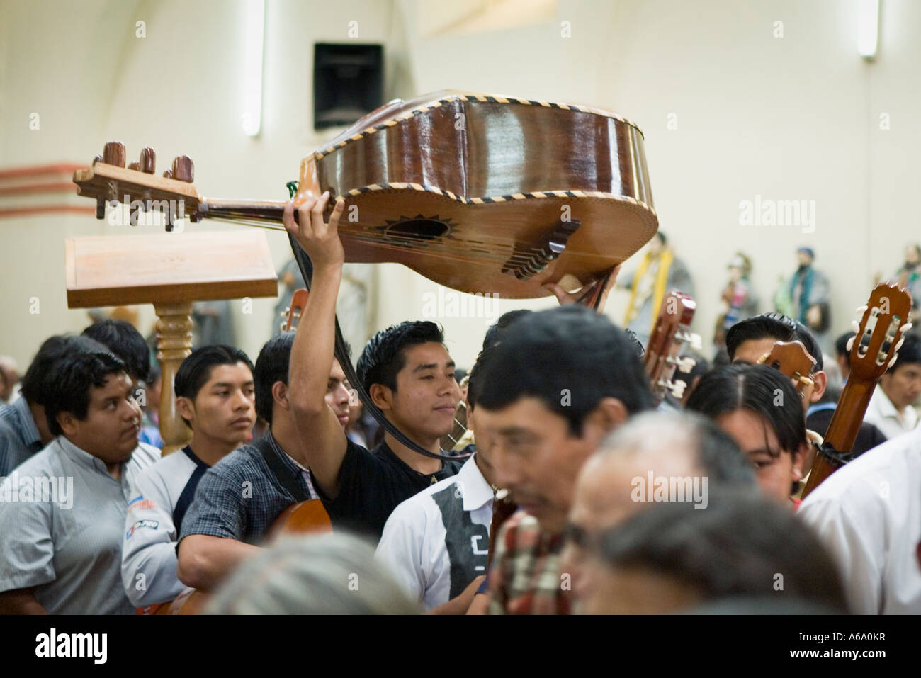 Carrying guitarron acoustic bass guitar out of church Santiago Atitlan Guatemala - Stock Image