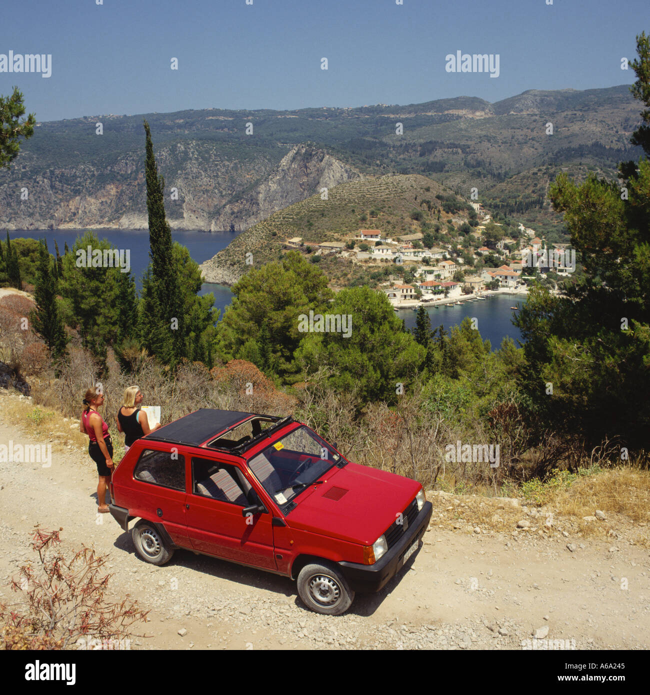 Two girls standing by red hire car reading a map and overlooking sea at Assos Cephalonia Island Ionian Islands The Stock Photo