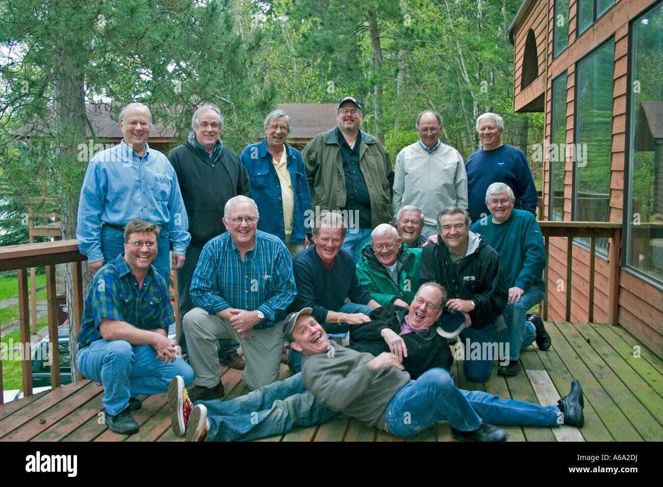 Photographer in black shirt trying to put a smile on a bunch of seasoned fishermen. Nisswa Minnesota USA - Stock Image