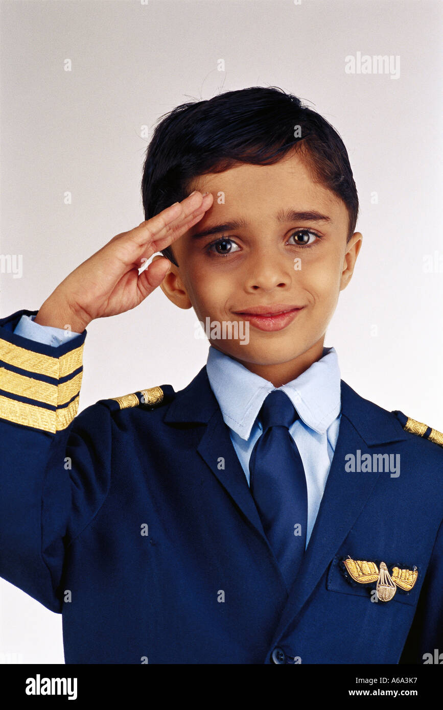 Young Indian boy saluting fancy dress of airline Pilot Model Release Number 496 - Stock Image