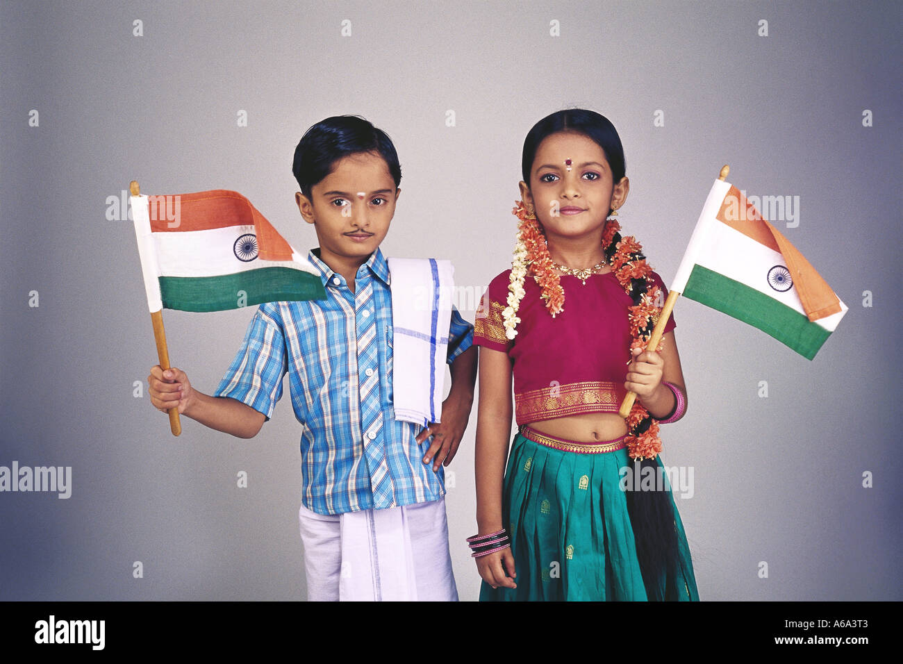 7691bfb9d2 South Indian boy girl wearing fancy dress traditional costume holding the  Indian Flag