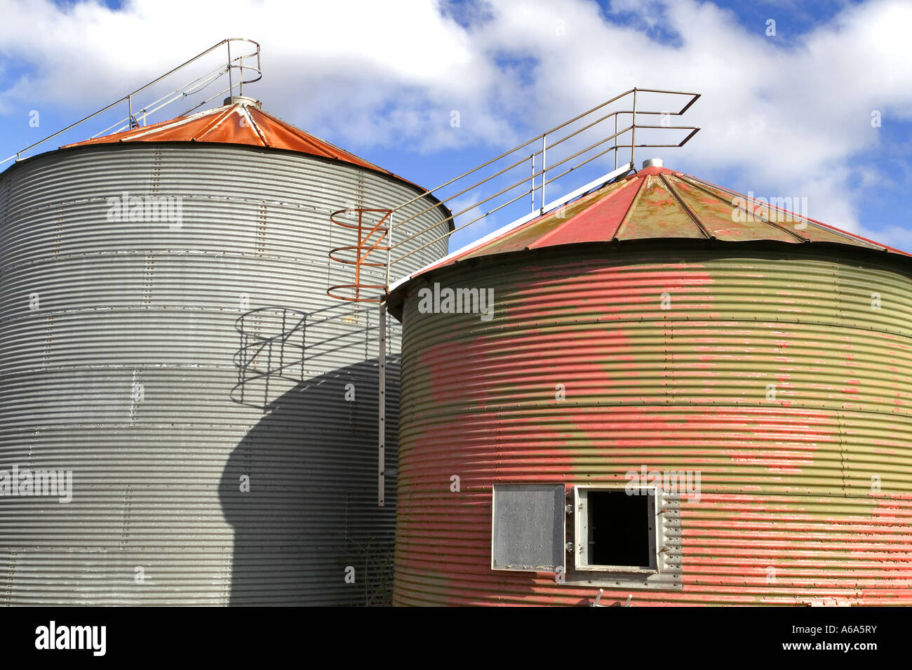 Pair of old grain drying silo s against a blue cloudy sky - Stock Image