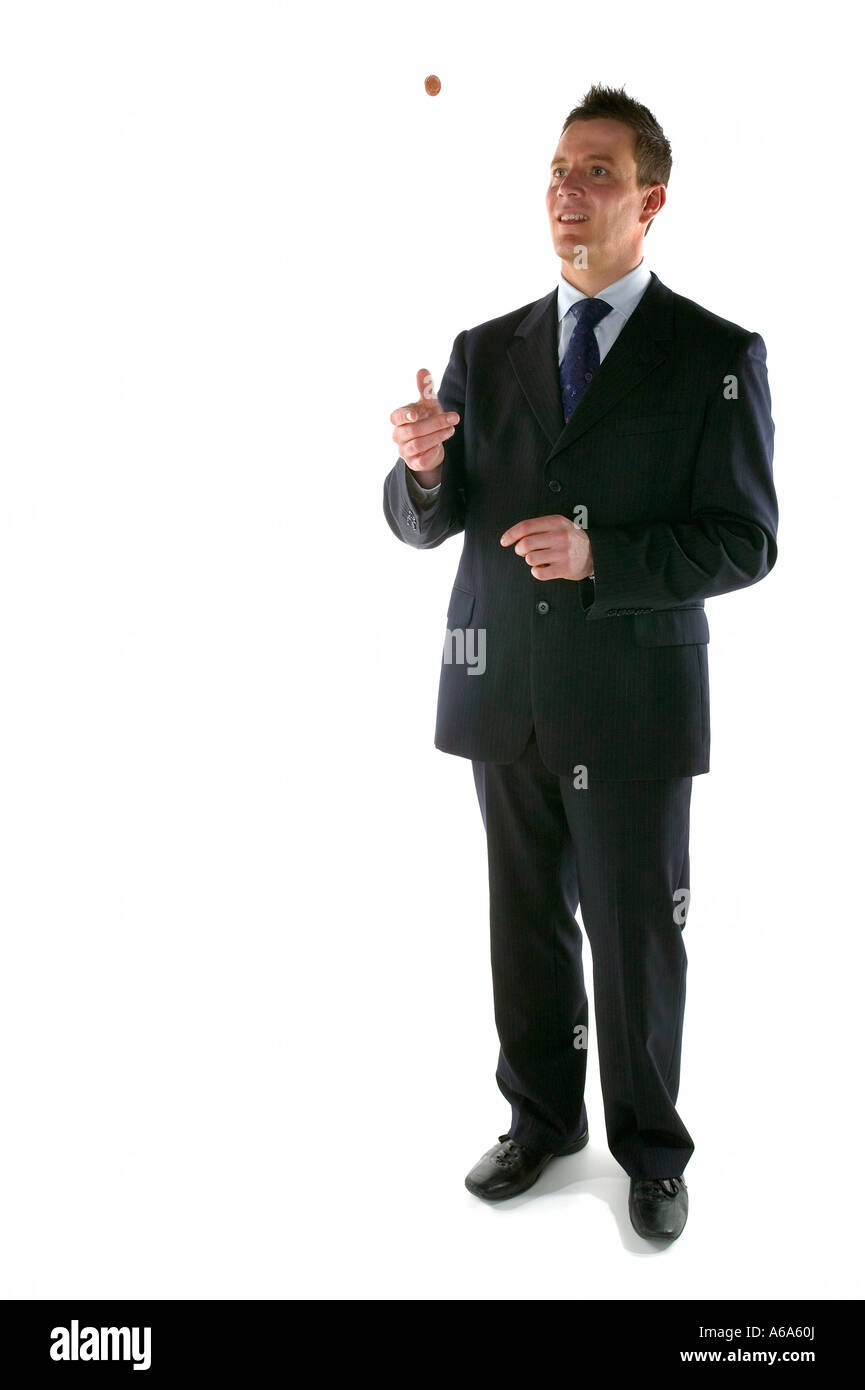 Businessman tossing a coin in the air - Stock Image
