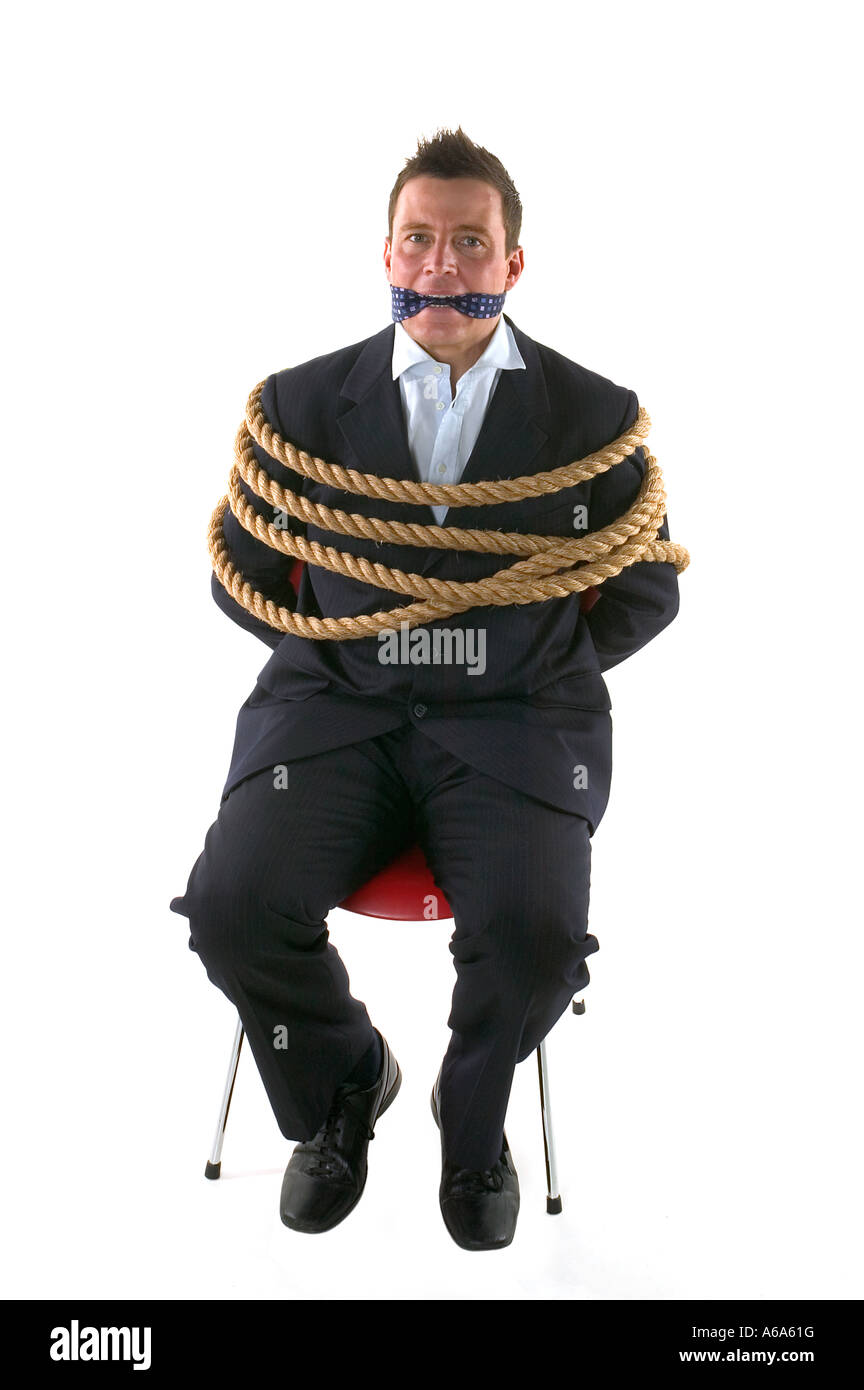 Businessman tied up with rope and gagged with his own tie isolated on a white background - Stock Image