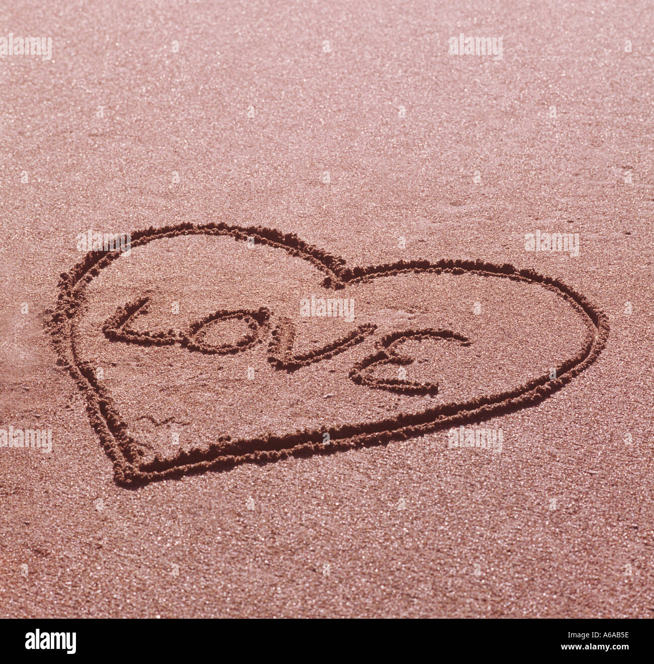 Valentine love symbol drawn in sand at beach - Stock Image
