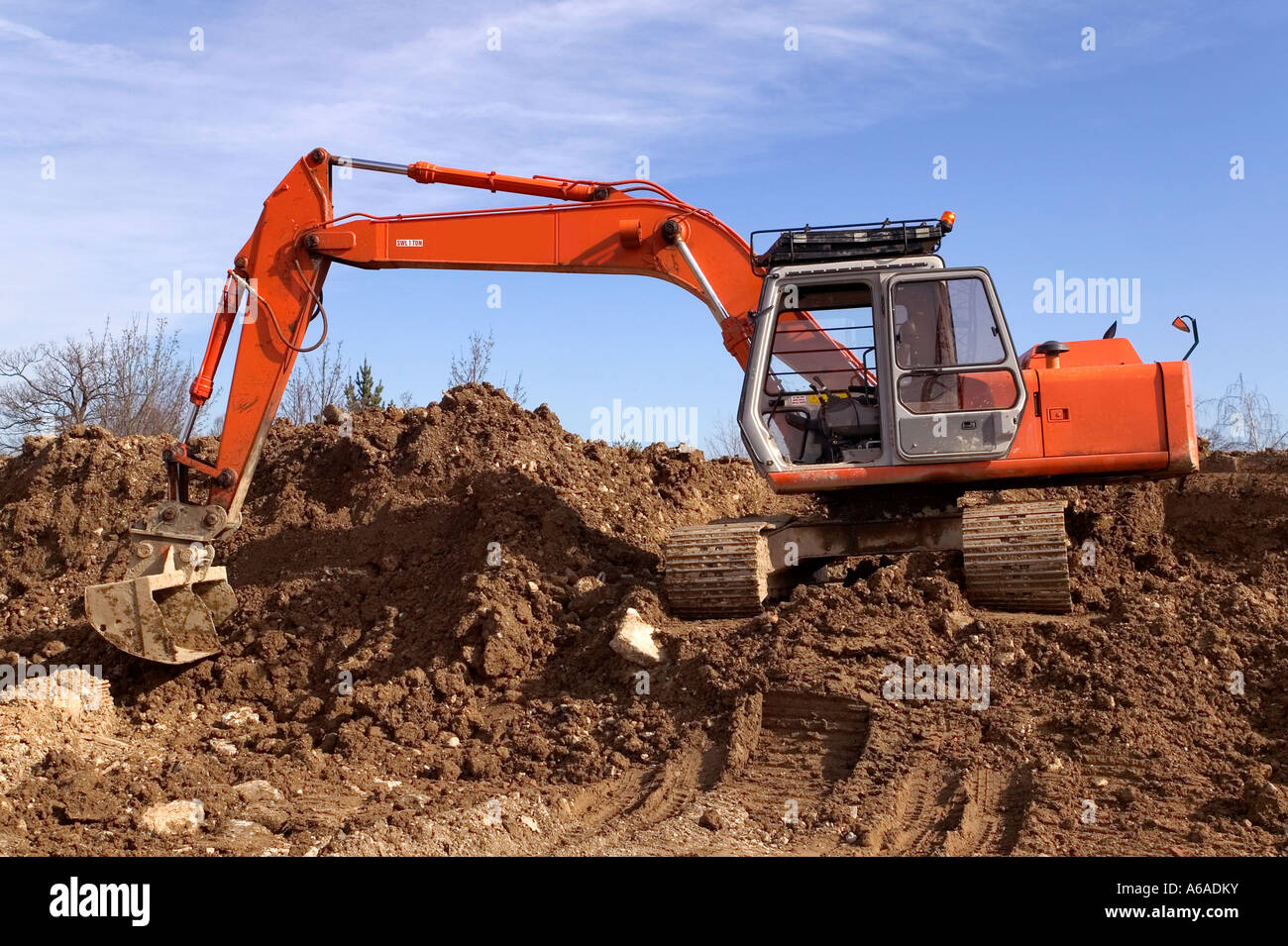 Construction digger on a mound of earth - Stock Image