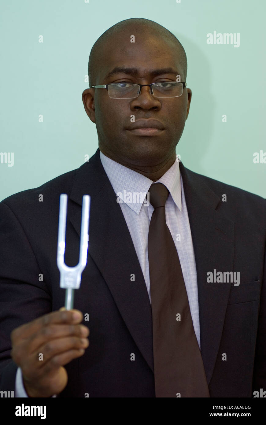 Portrait of a consultant with a tuning fork in his hand looking to camera  UK - Stock Image