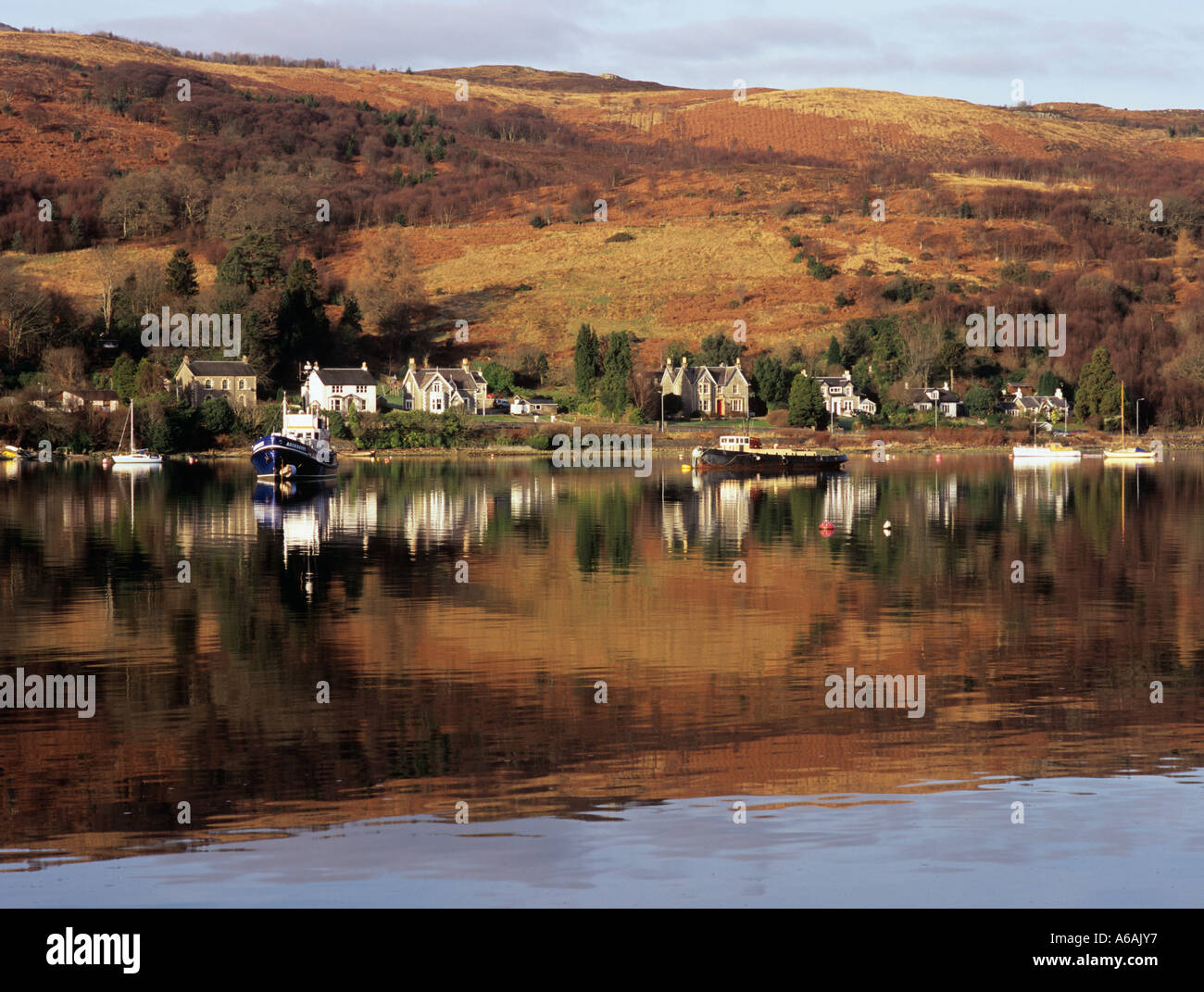HILLSIDE and VILLAGE HOUSES beside tidal Gare Loch reflected in calm water. Garelochhead Argyll Bute Scotland UK - Stock Image