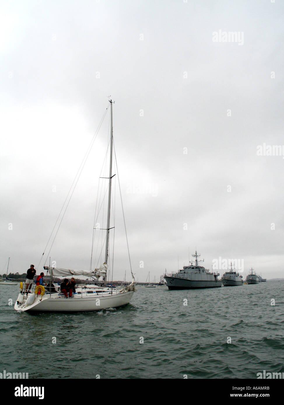 yacht sailing towards navy battleships, portsmouth harbour, hampshire, england. - Stock Image