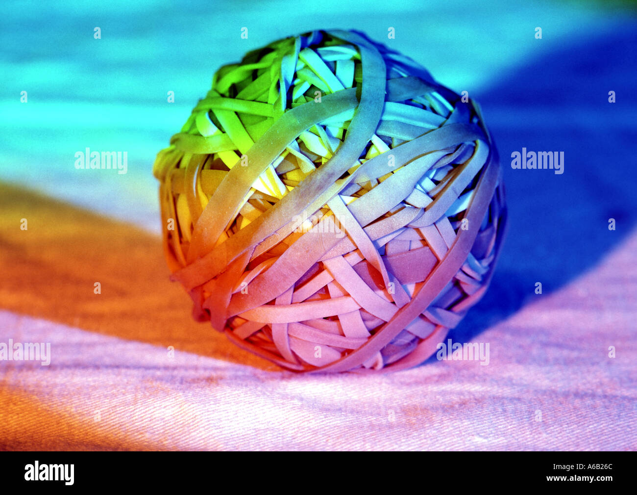 Colourful photo of ball of elastic bands as concept type image eg banding together office relationships stretch the imagination etc - Stock Image