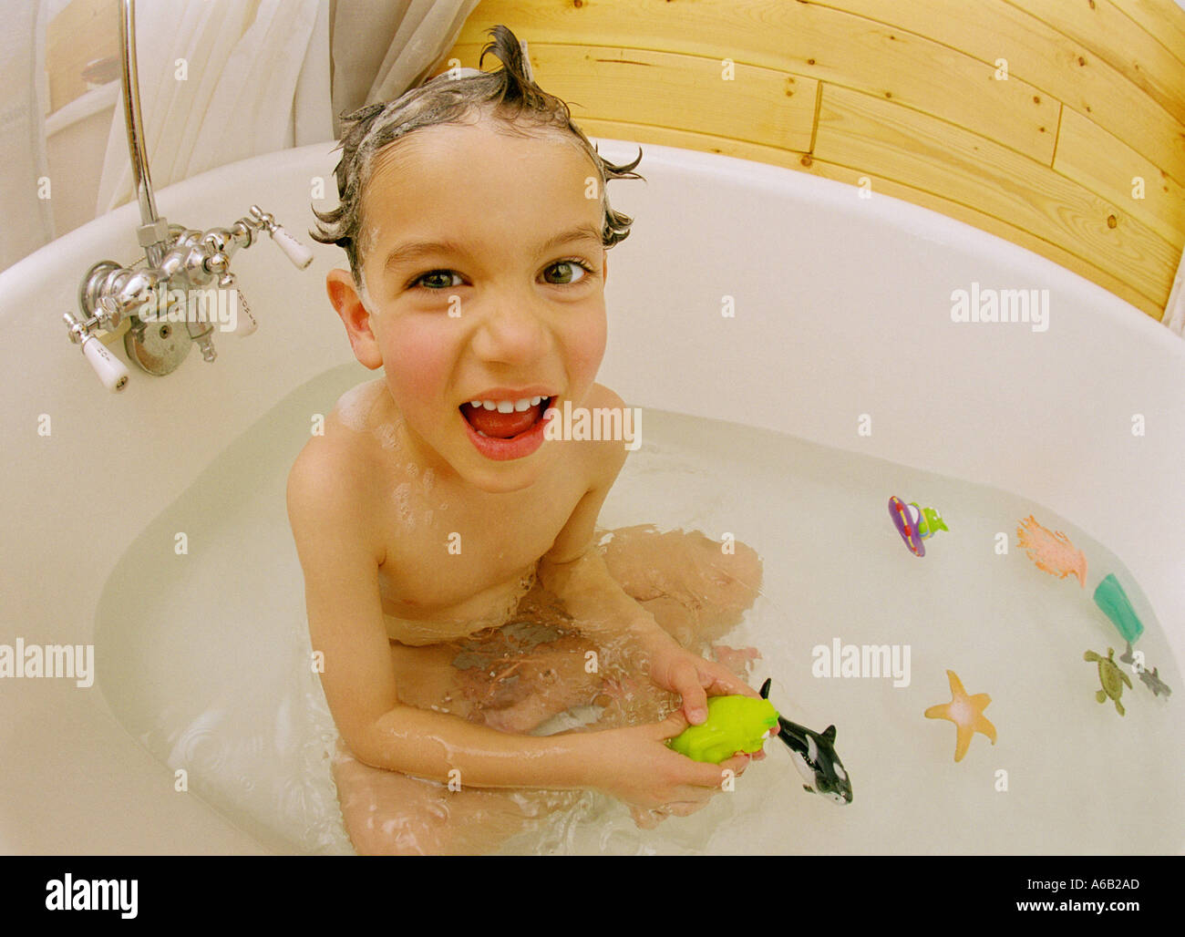 5 Year Old Boy In Bathtub Playing With Toys