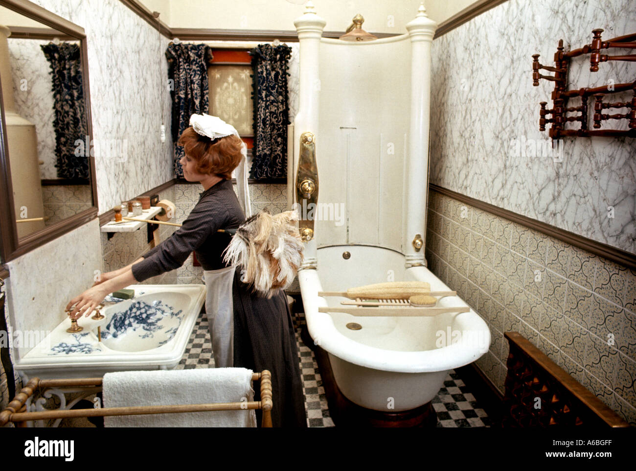 A MAID IN VICTORIAN DUSTS IN PERIOD COSTUME A VICTORIAN BATHROOM - Bathroom maid