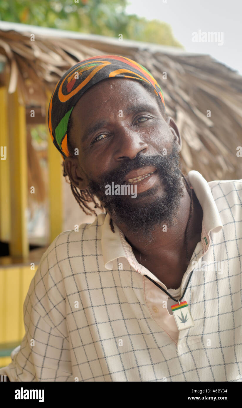 A color vertical image of a rastafarian man wearing a polo type shirt with his hair in a banadana and a ganja pendant around his - Stock Image