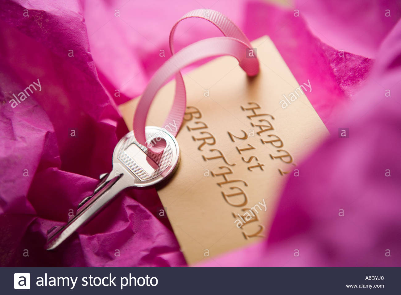 House key on gold gift tag saying Happy 21st Birthday - Stock Image