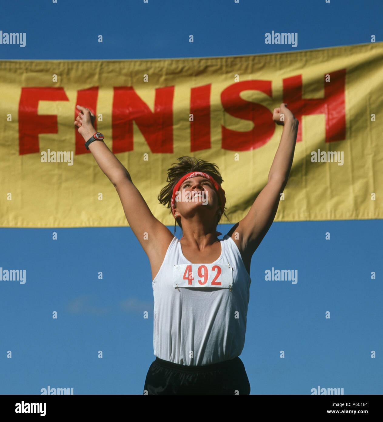 Track Winner: Female Runner Crossing Finish Line At Track Meet As Winner
