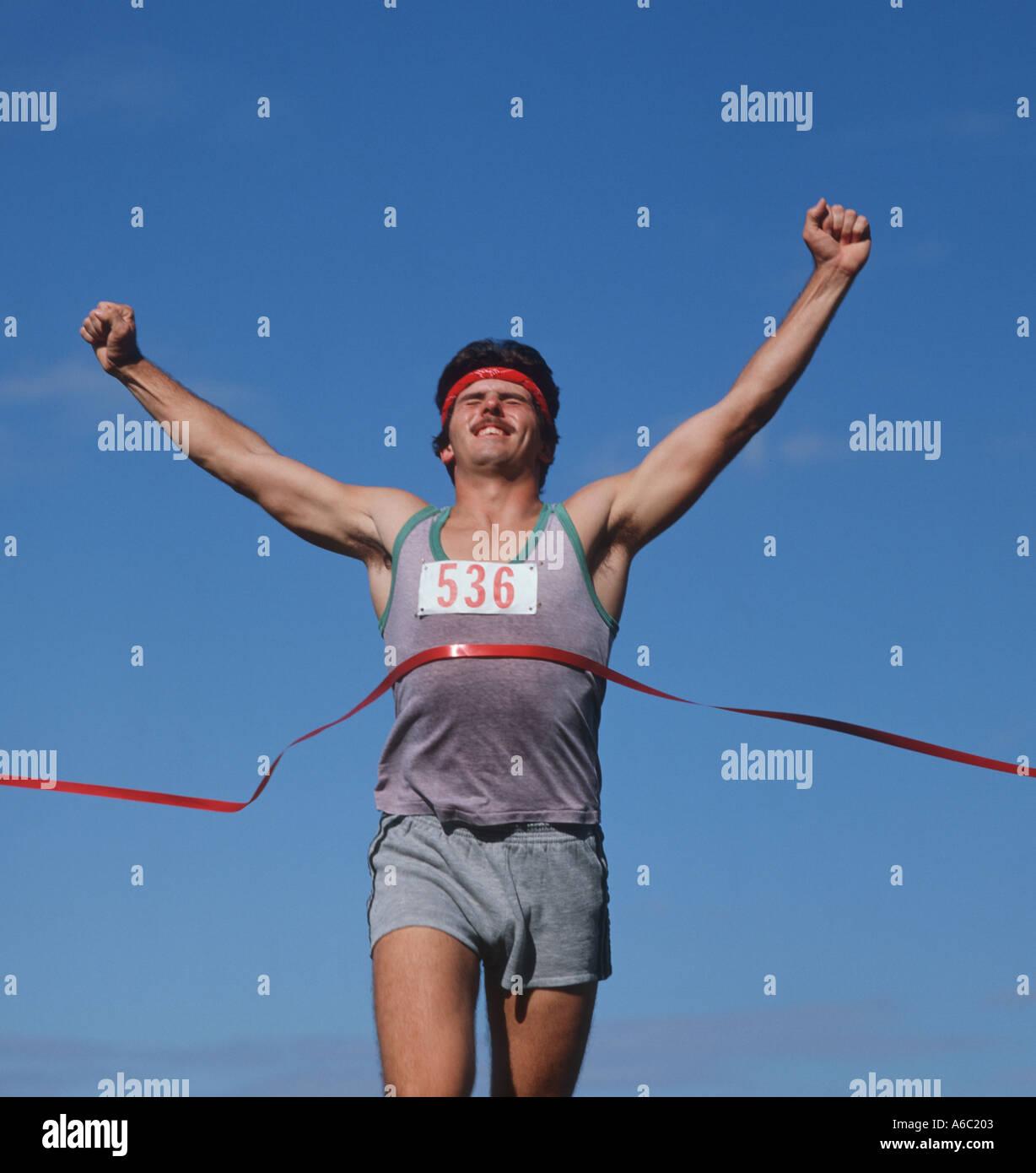 quality design 1062f ba06b male runner crossing finish line ribbon at track meet race - Stock Image