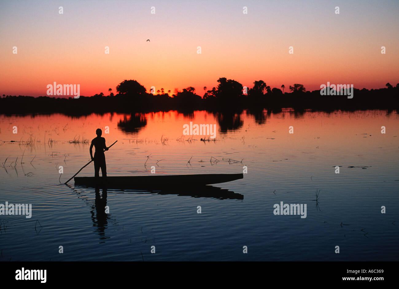 Botswana people Bayei mokoro poler at sunset in the Okovango Delta Okovango Botswana - Stock Image