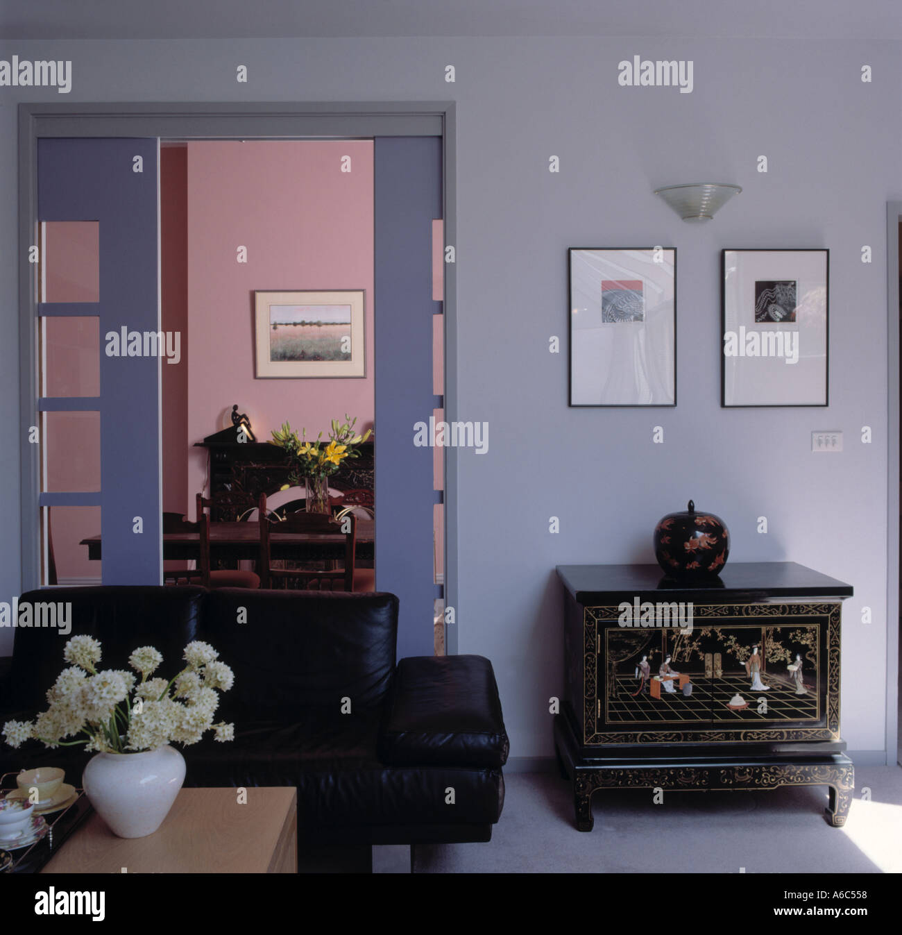 https://c8.alamy.com/comp/A6C558/oriental-chest-and-black-leather-sofa-in-pale-blue-modern-living-room-A6C558.jpg