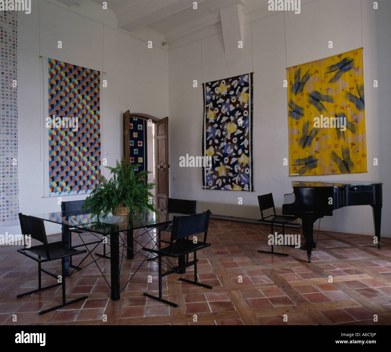 Large Abstract Paintings On Walls Of Modern Diningroom With Grand Piano And  Terracotta Tiled Floor