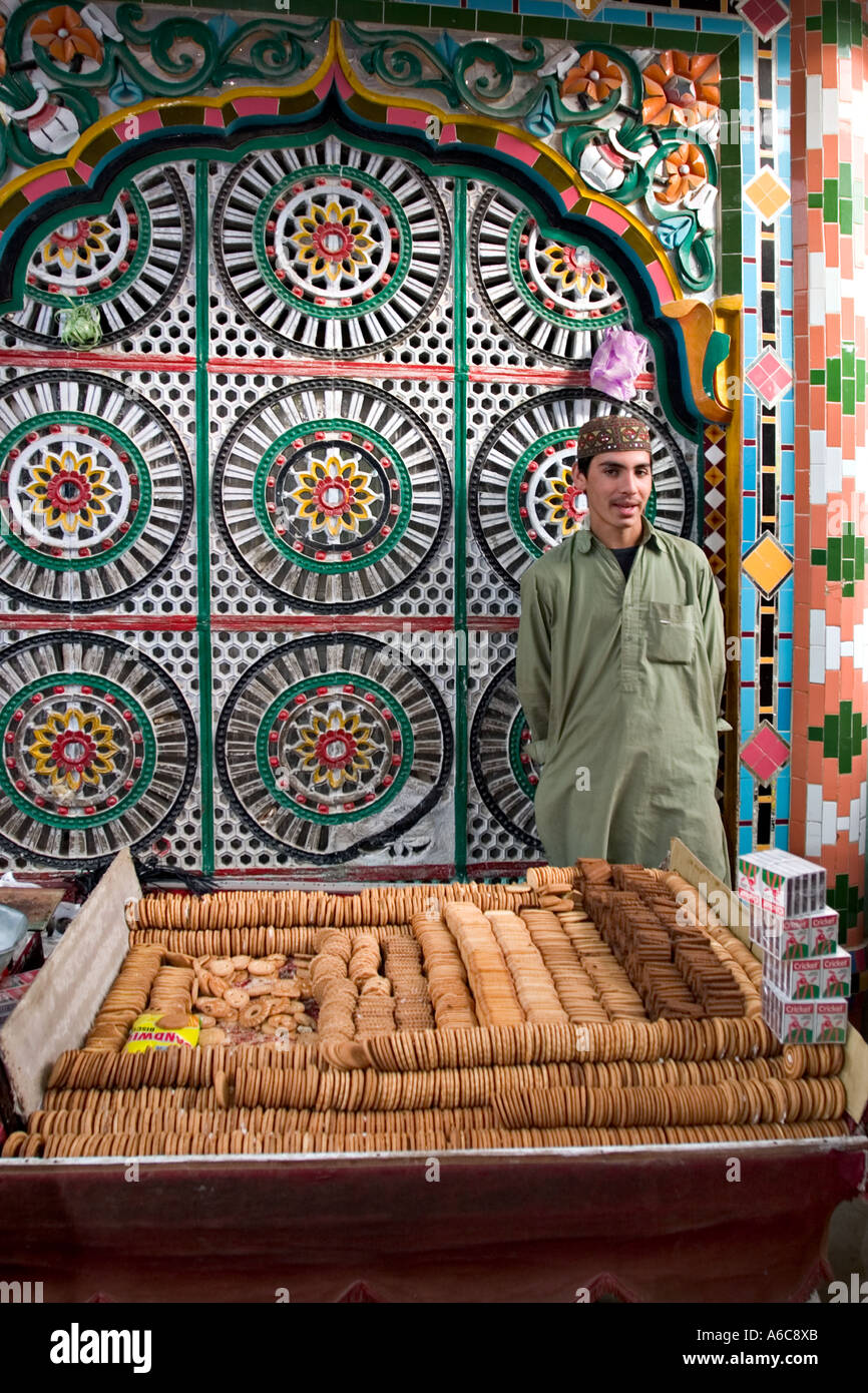 Boy sells biscuits outside mosque, Hassan Abdal market, Pakistan Stock Photo