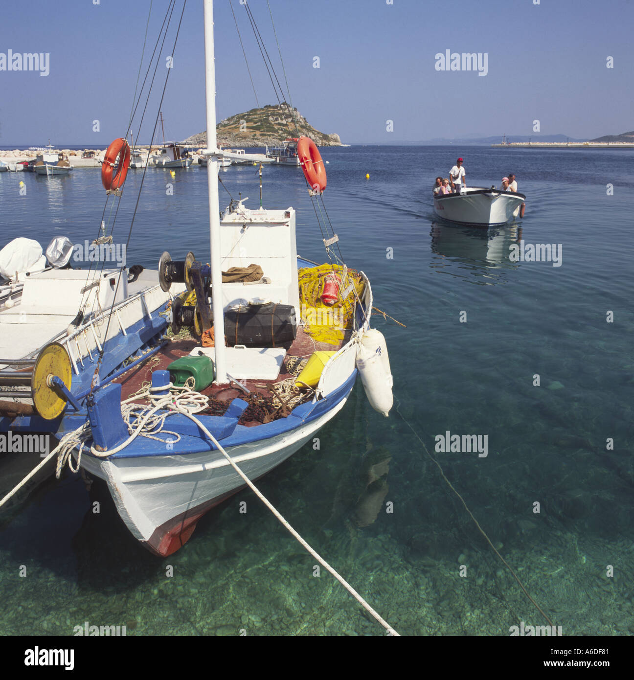 Colourful traditional style little Greek fishing boat moored at quayside in Agios Nikolaos port of Zakynthos The Stock Photo