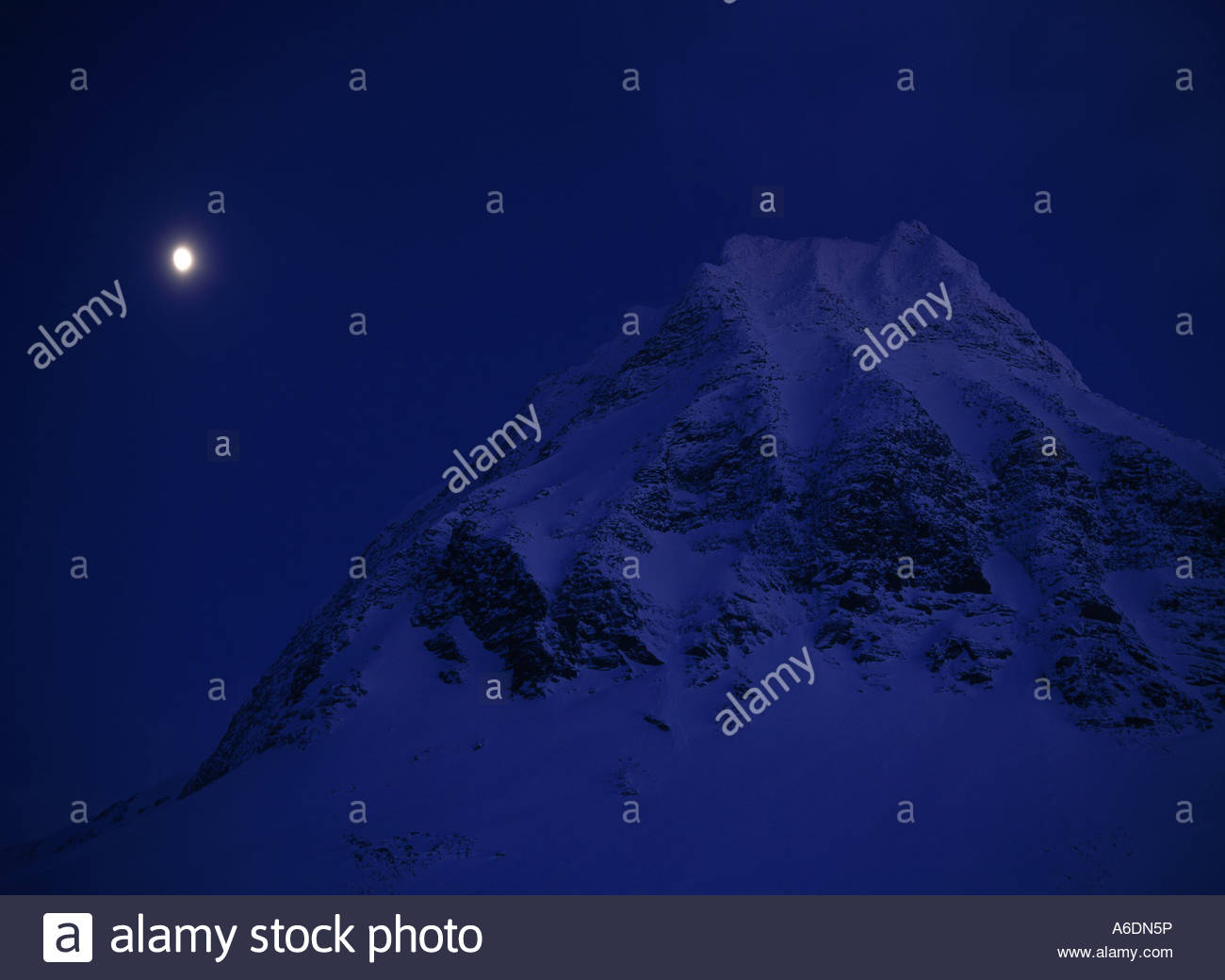 Moon glowing over mountain in the sky, Mt Kebnekaise, Lapland, Sweden - Stock Image