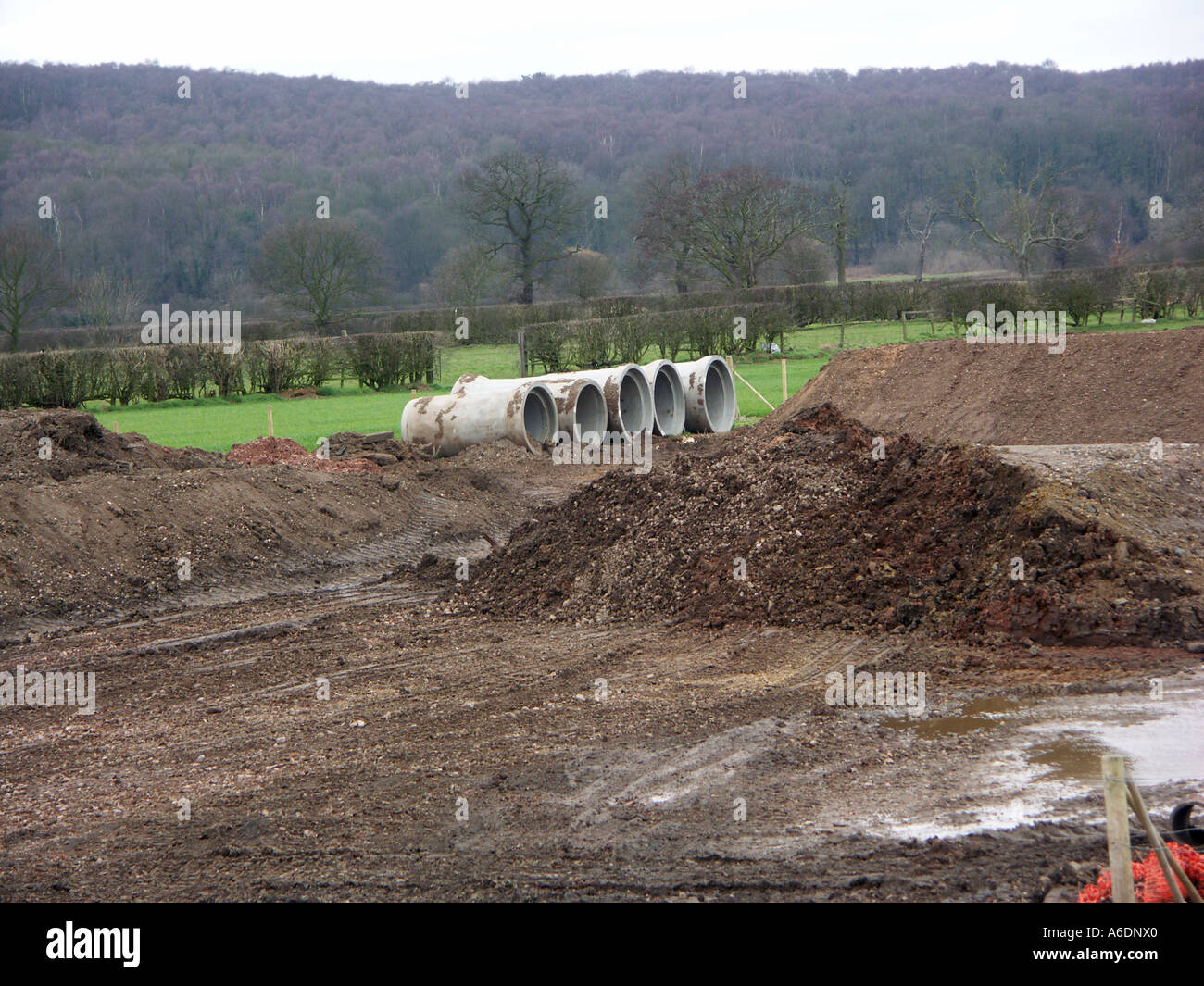 Large pre-cast concrete sewerage or drainage pipes on a green field construction or building site. & Large pre-cast concrete sewerage or drainage pipes on a green field ...
