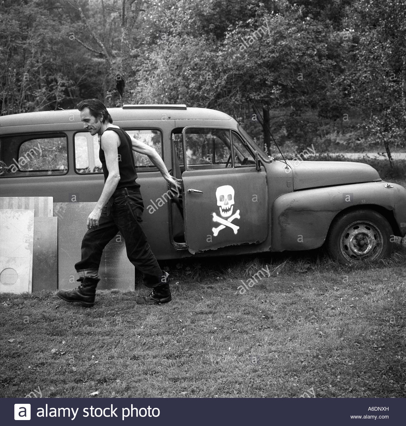 A man closing the door of an old car with the jolly Roger on it. Stockholm - Stock Image