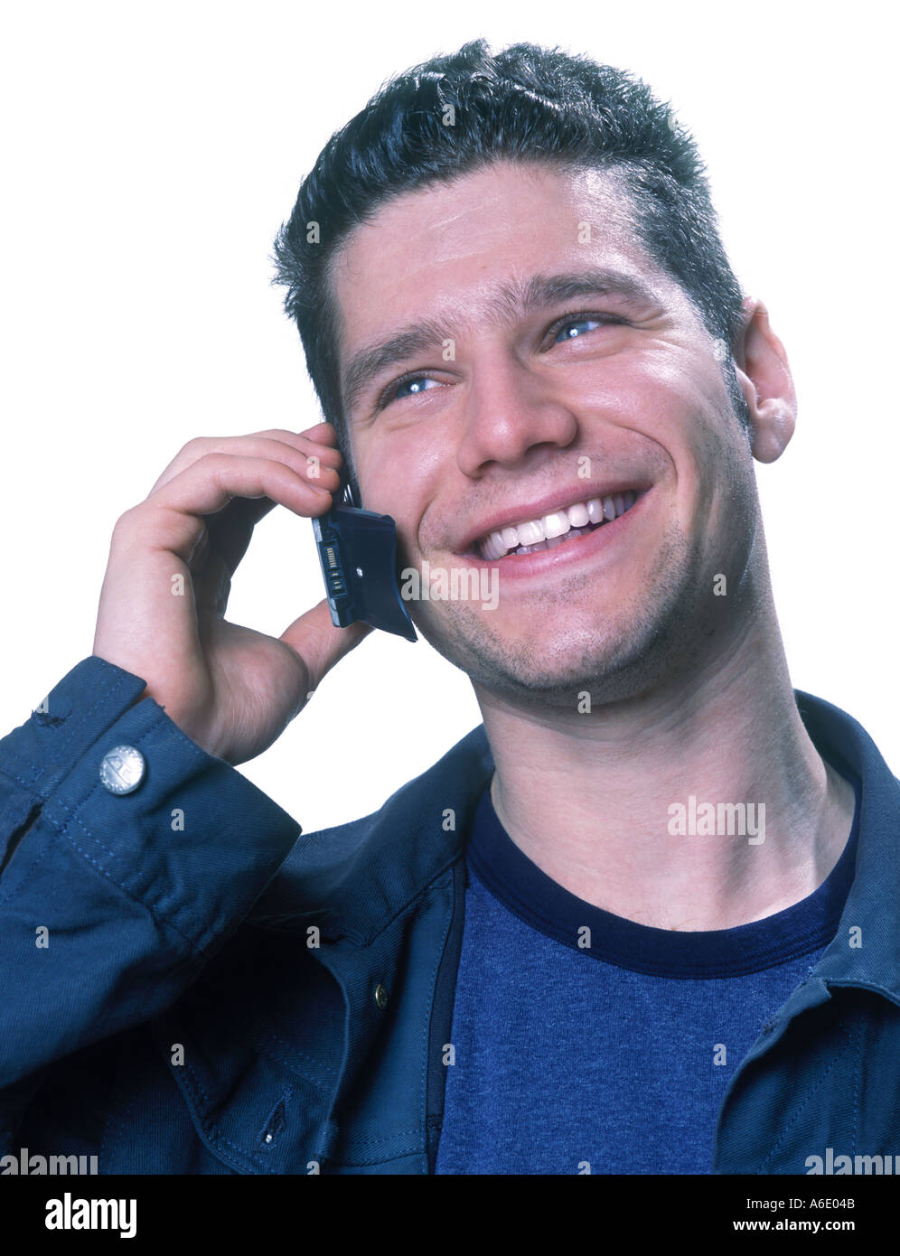 Young man laughing while talking on cellphone - Stock Image