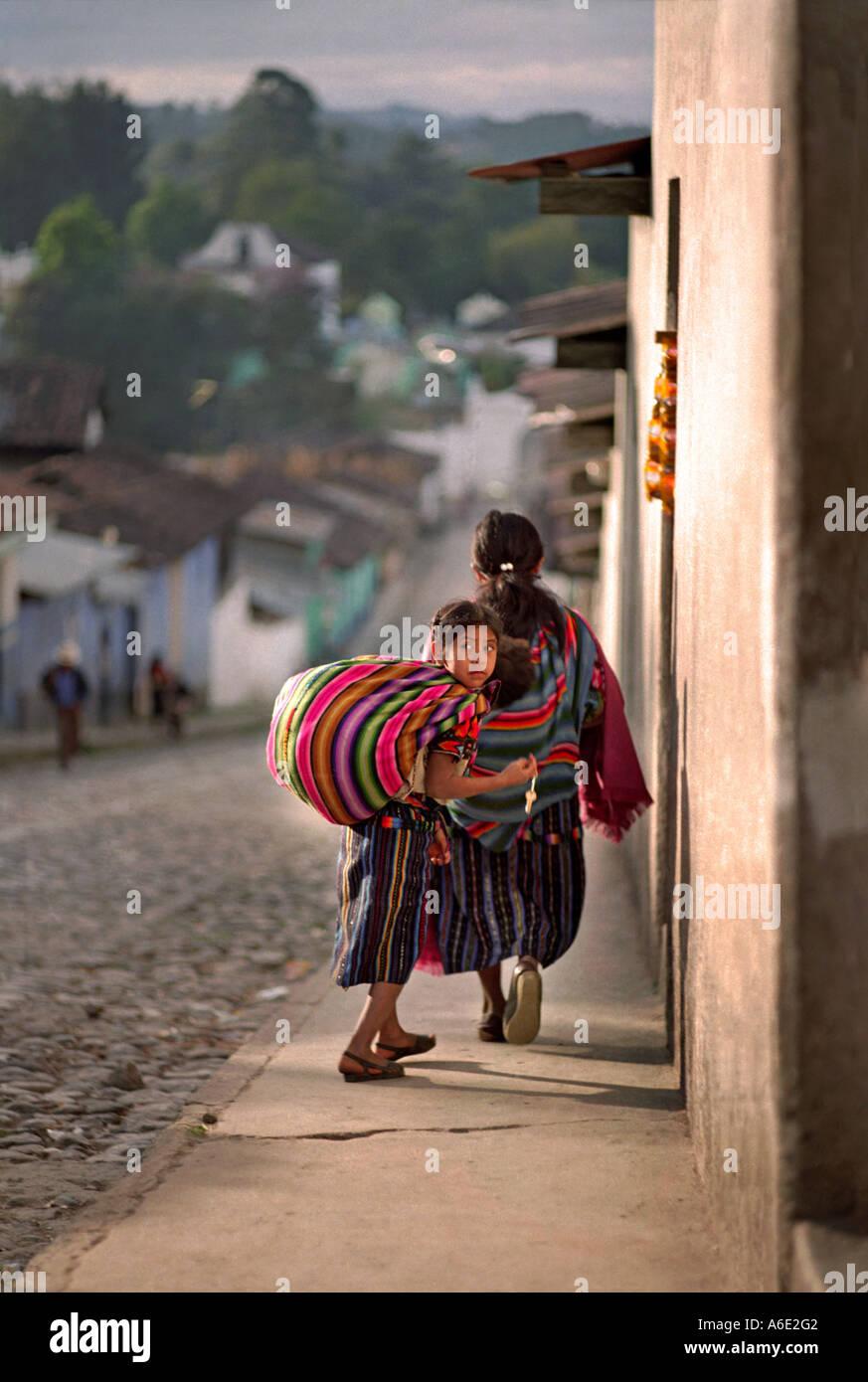 Guatemala Chichicastenango Young Maya girl in traditional village dress walking home Central America - Stock Image