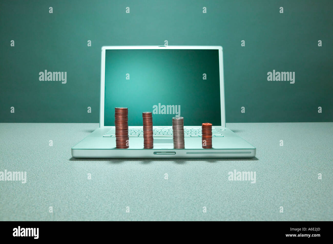 Laptop computer with piles of coins sitting on it Stock Photo