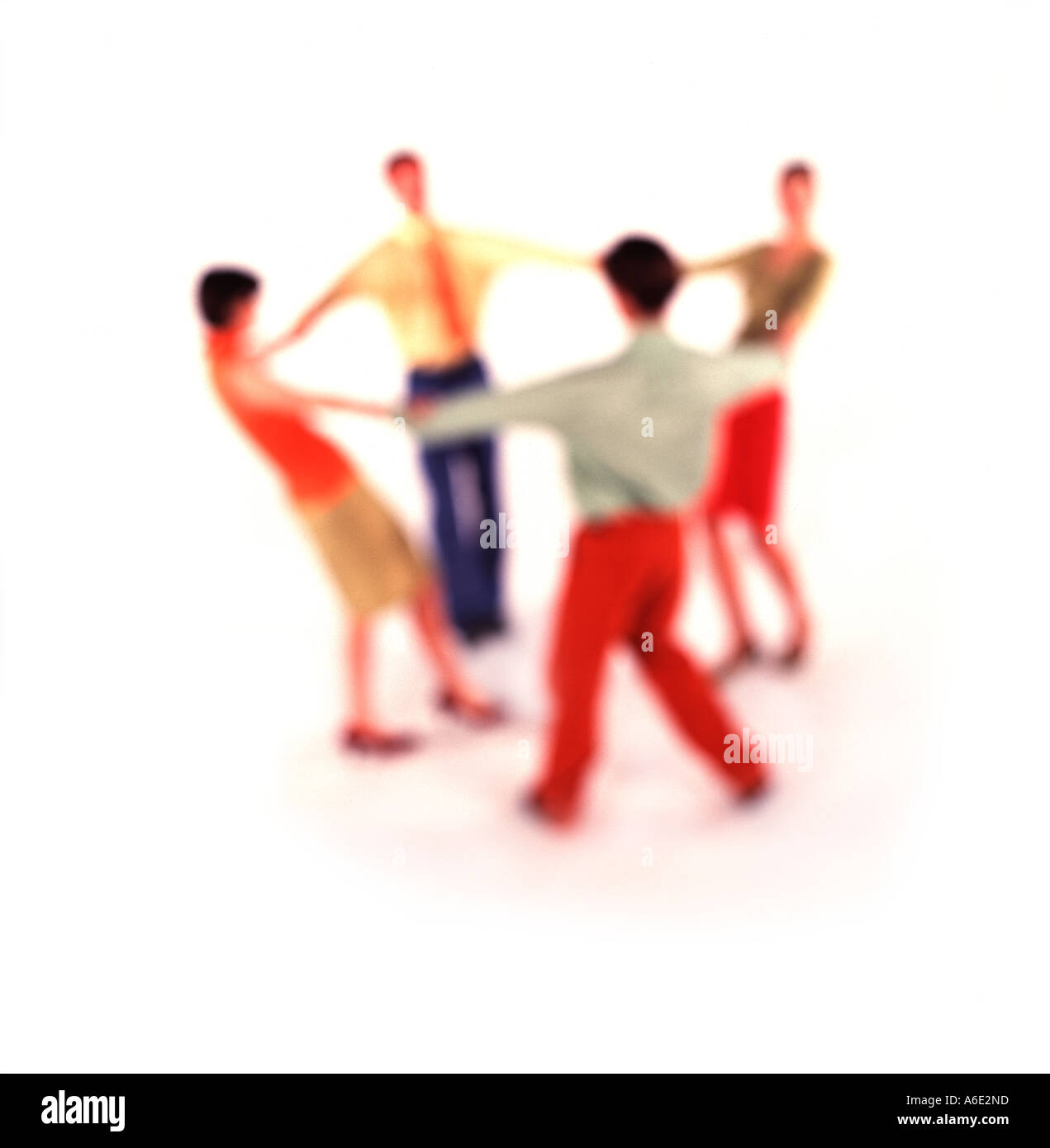 Group of 4 Business people holding hands in circle. Soft Focus. - Stock Image