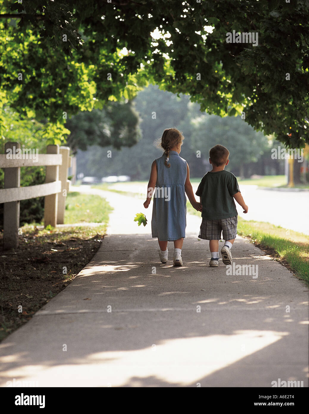 Brother and Sister (2 and 5 years) walking hand in hand down sidewalk Stock Photo