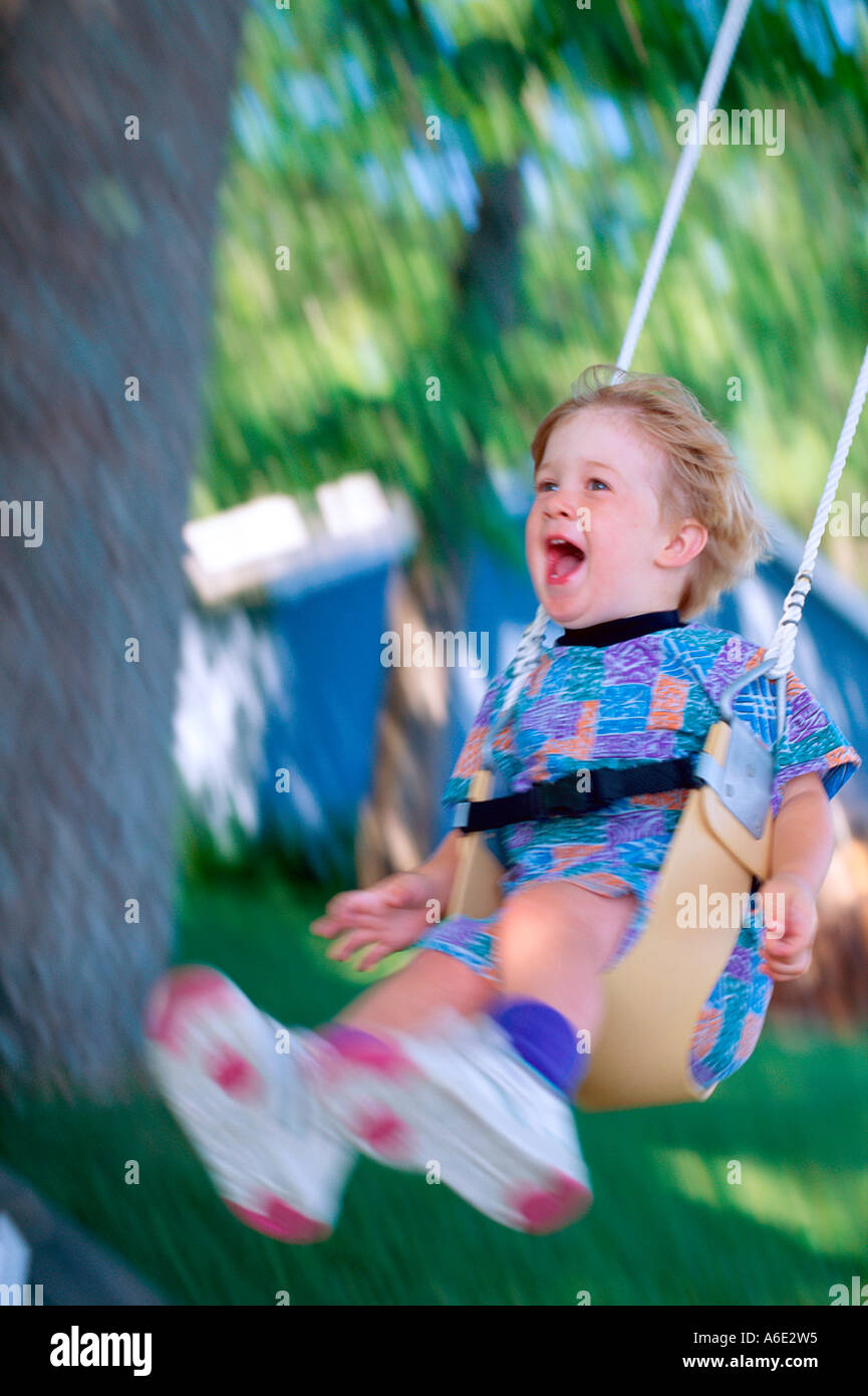 3 Year old boy yelling with excitement while swinging on swing Stock Photo