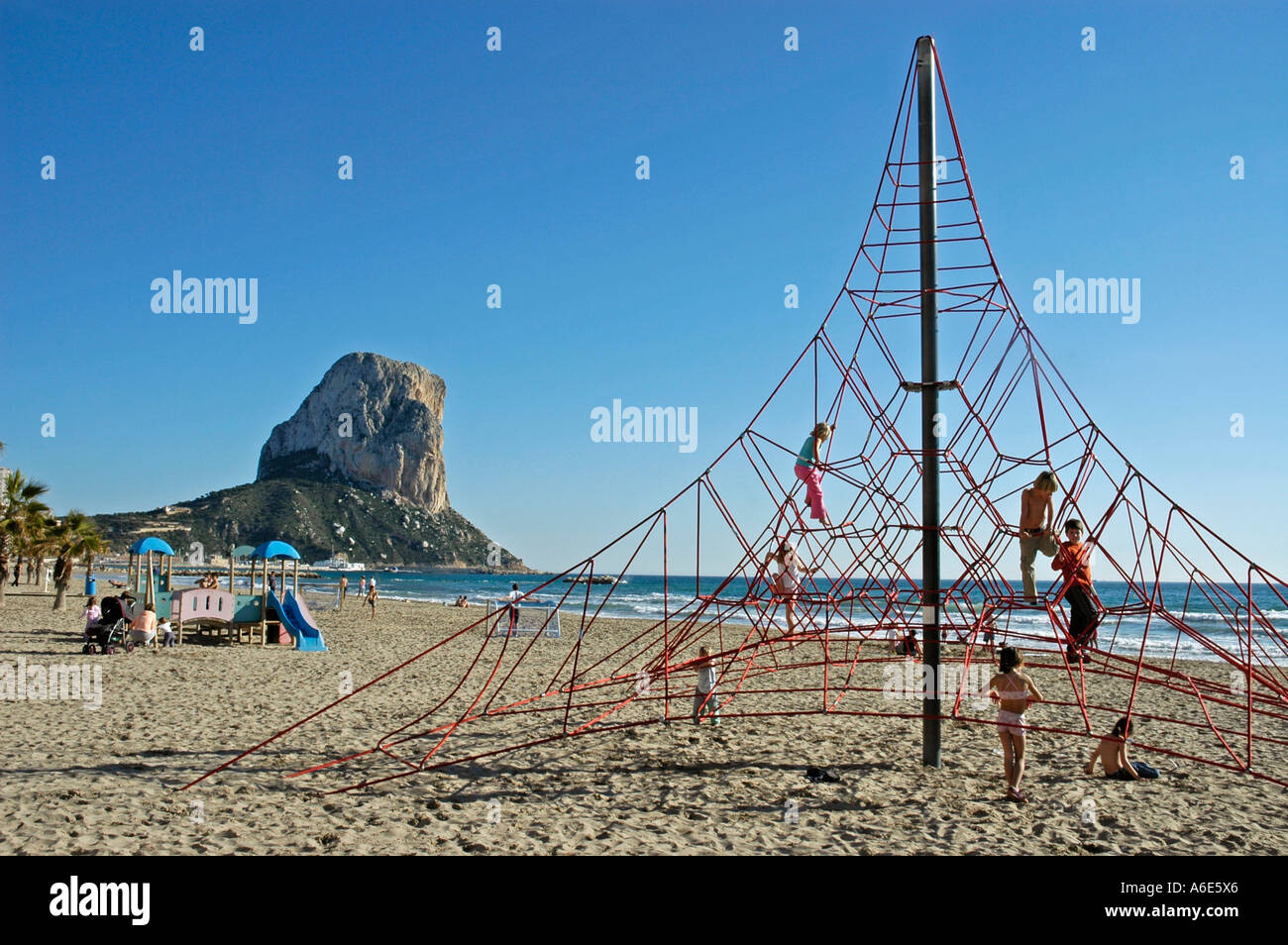 Children play in climbing scaffold at the beach of Calpe, Penon de Ifach, Costa Blanca, Spain - Stock Image