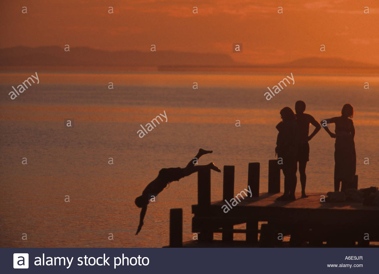 Children diving from at jetty - Stock Image