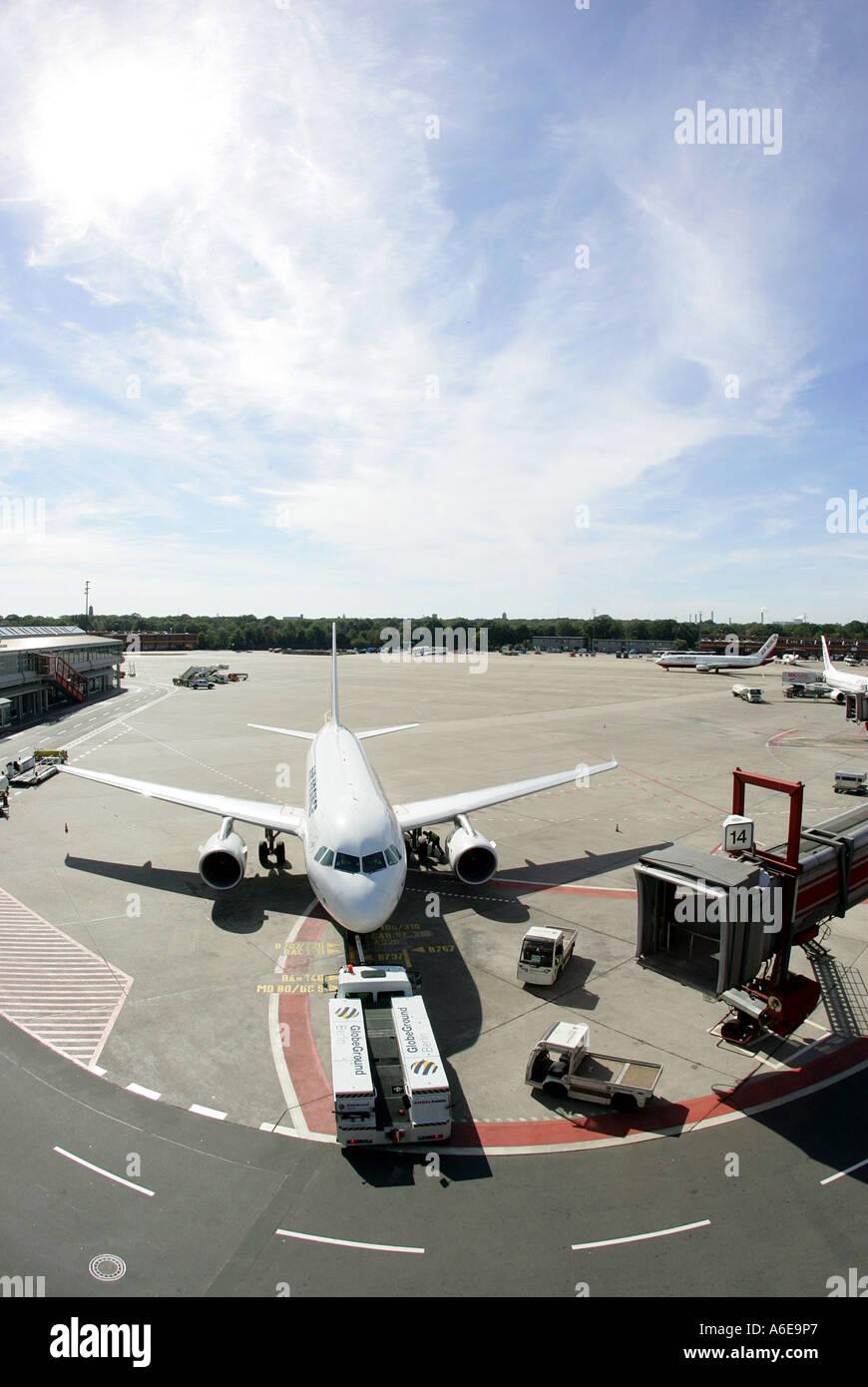Airplane and boarding bridge at Tegel airport, Berlin - Stock Image