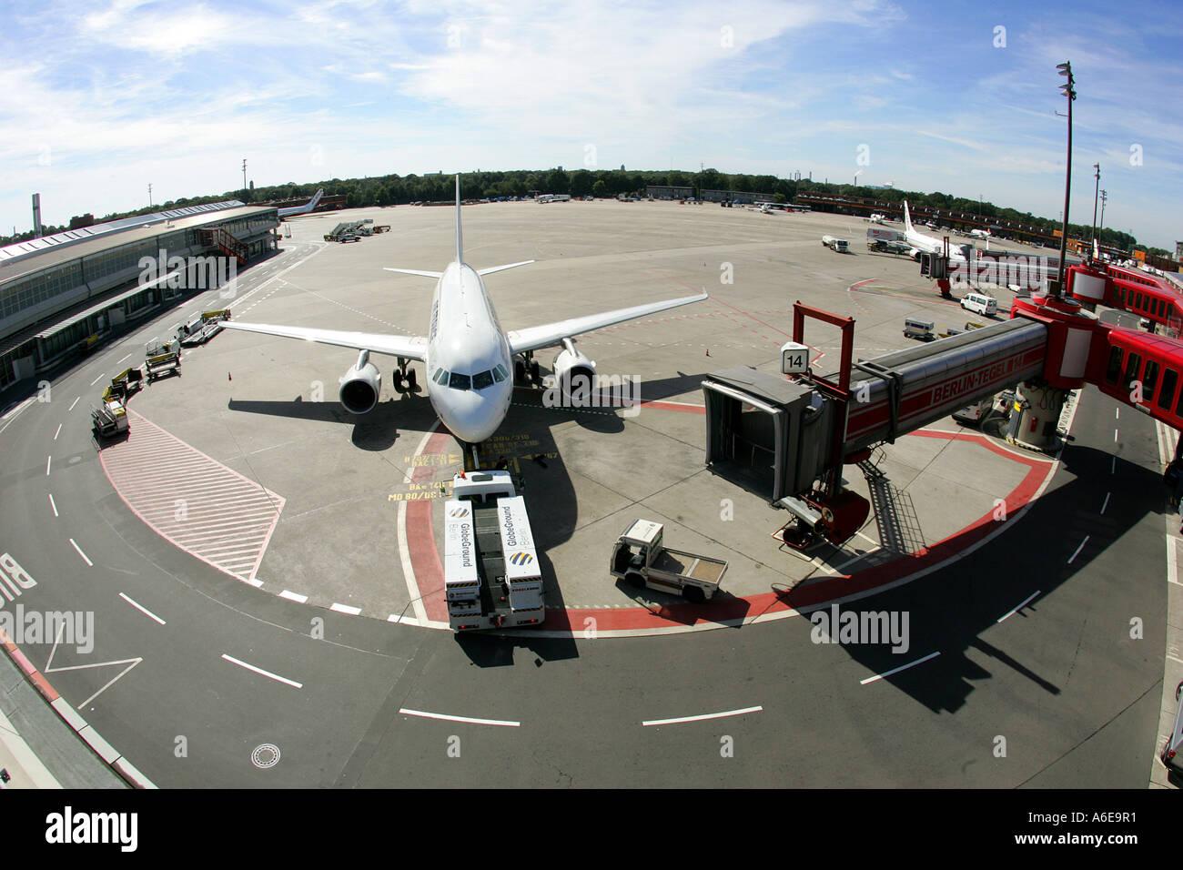 Airplane and boarding bridges at Tegel airport, Berlin - Stock Image