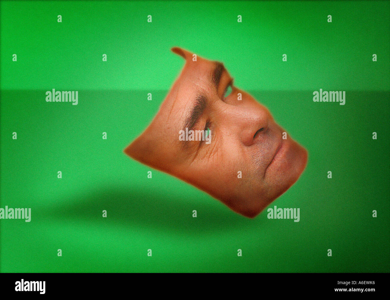 Mans face in the form of a mask against green background - Stock Image