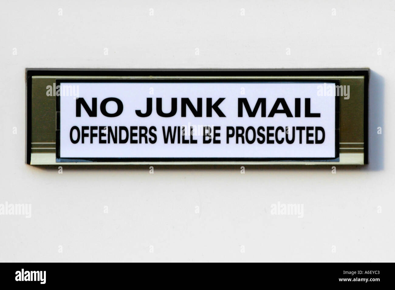 NO JUNK MAIL OFFENDERS WILL BE PROSECUTED notice attached to a letter box on a UPVC front door UK - Stock Image