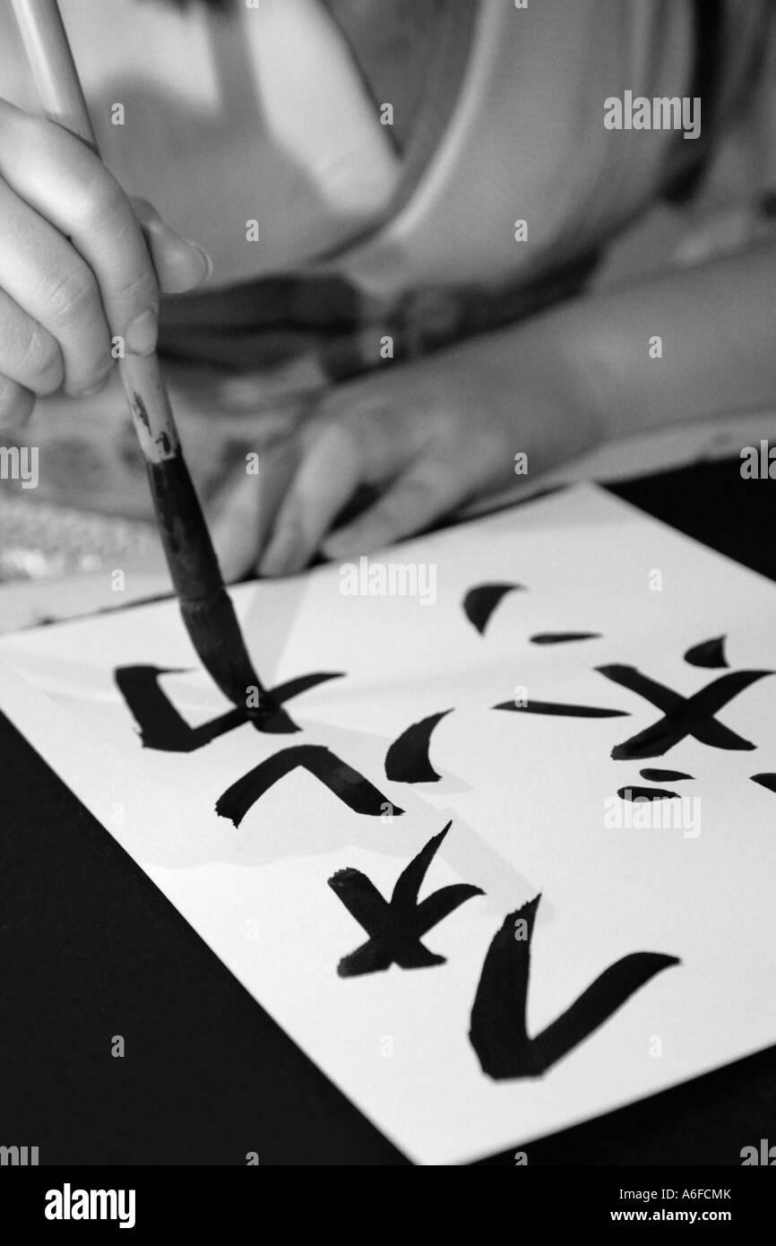 asian woman paints Kanji characters Asiatische Frau malt Kanji Zeichen auf Papier - Stock Image