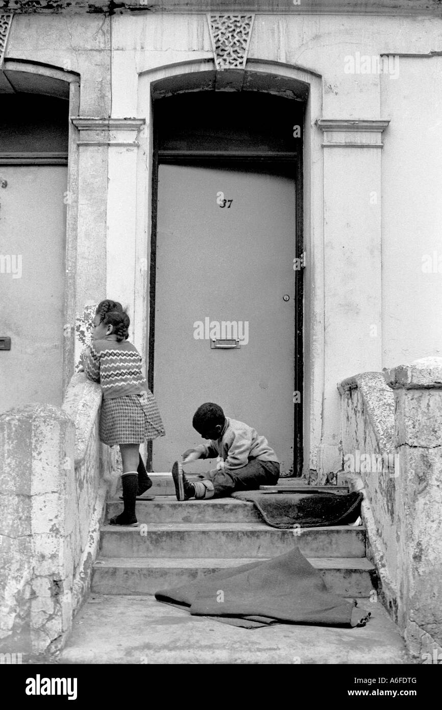 Children playing outside house in Notting Hill Gate London Uk 1975. - Stock Image