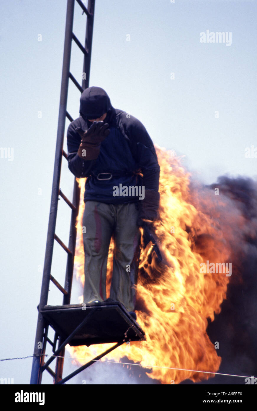 Stunt person at public display about to jump into water tank from top of tower having ignited flammable liquid on cape - Stock Image