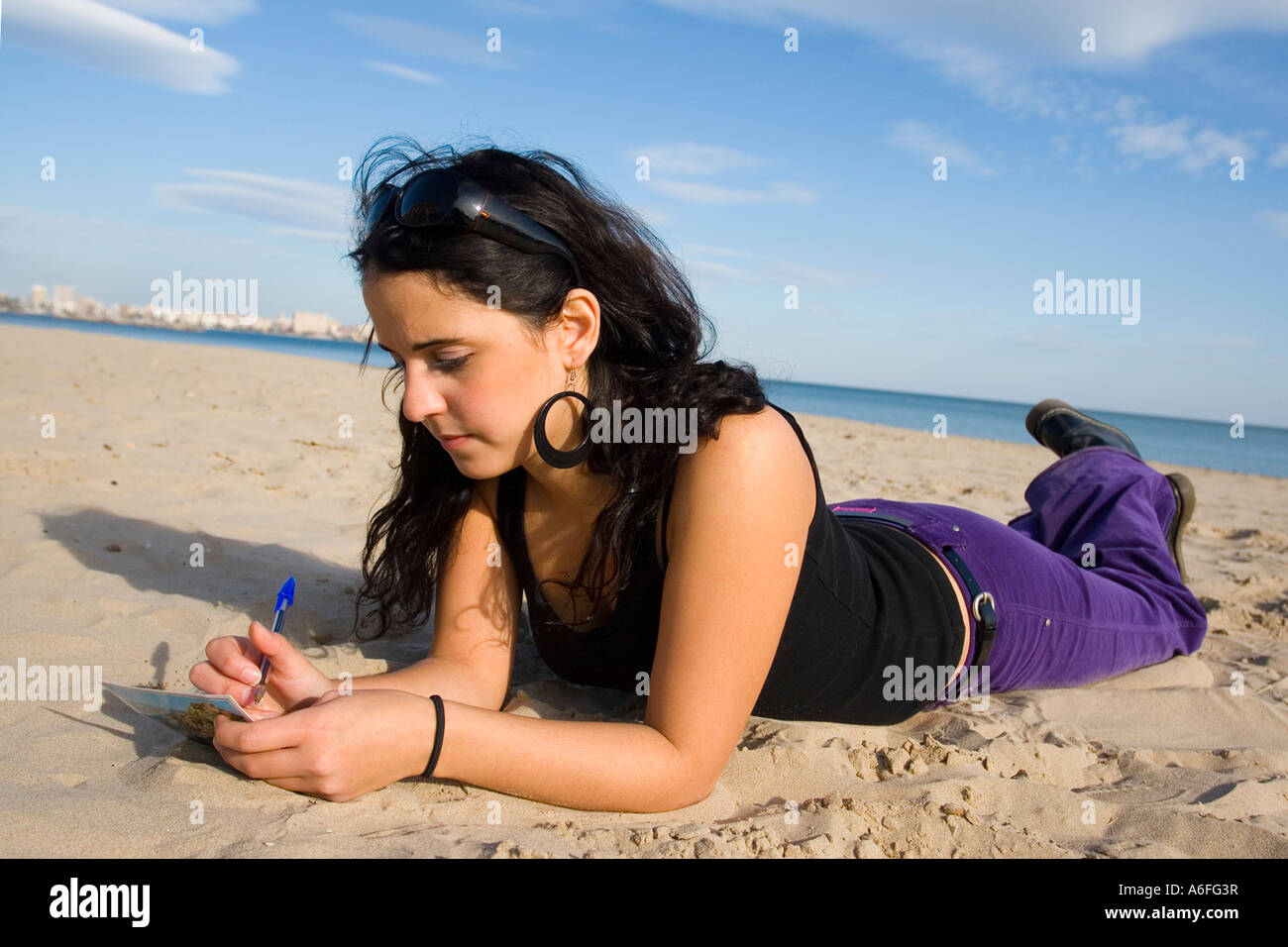 Young woman lying on beach. - Stock Image
