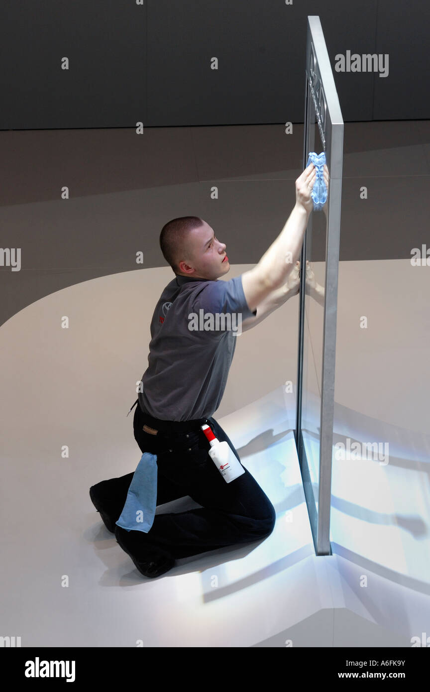 A worker at the Geneva Motor Show cleaning the glass of a display. Slight motion blur on his arm and hand - Stock Image
