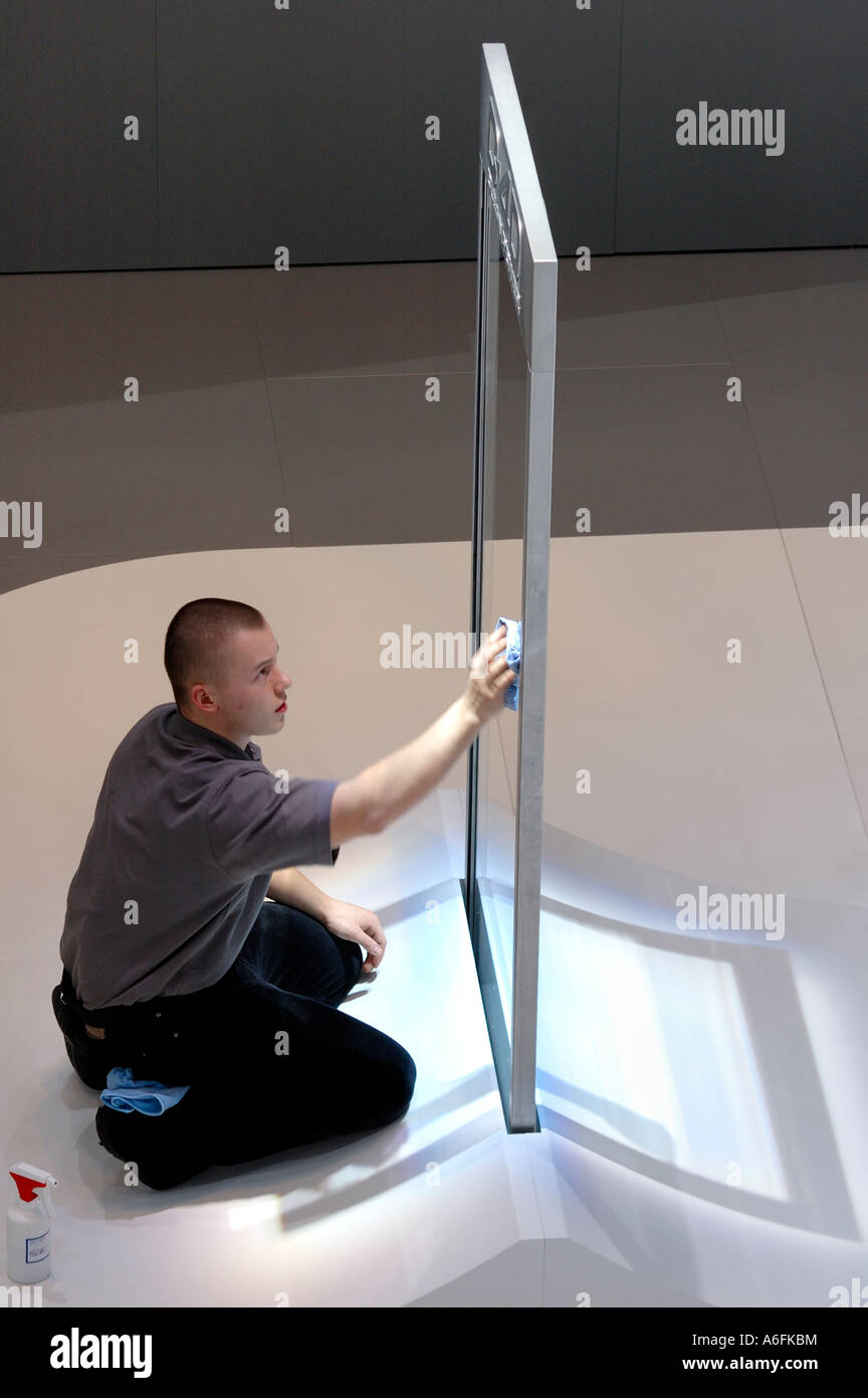 A worker at the Geneva Motor Show cleaning the glass panel of a display. Slight motion blur on his arm and hand - Stock Image