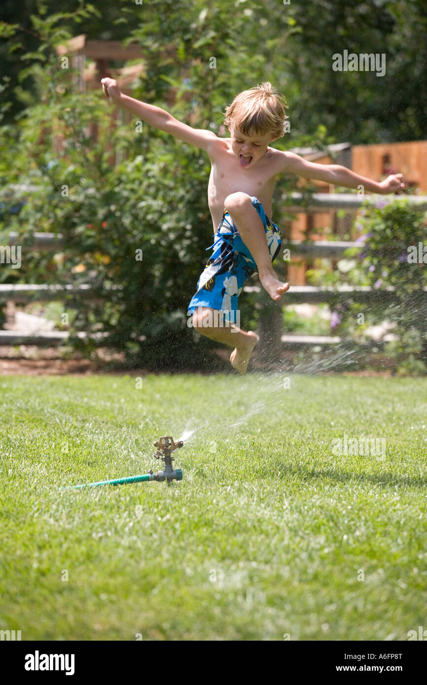 Child Running Through the Sprinklers - Stock Image