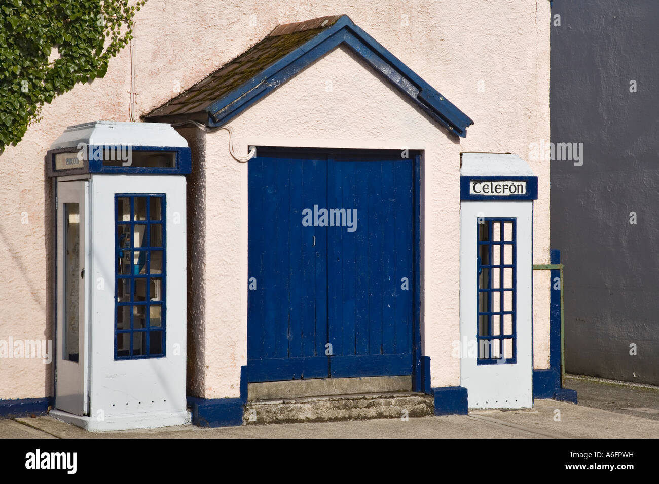 Traditional Irish telephone boxes by blue door on pink building in North Square on 'Ring of Kerry' tourist - Stock Image