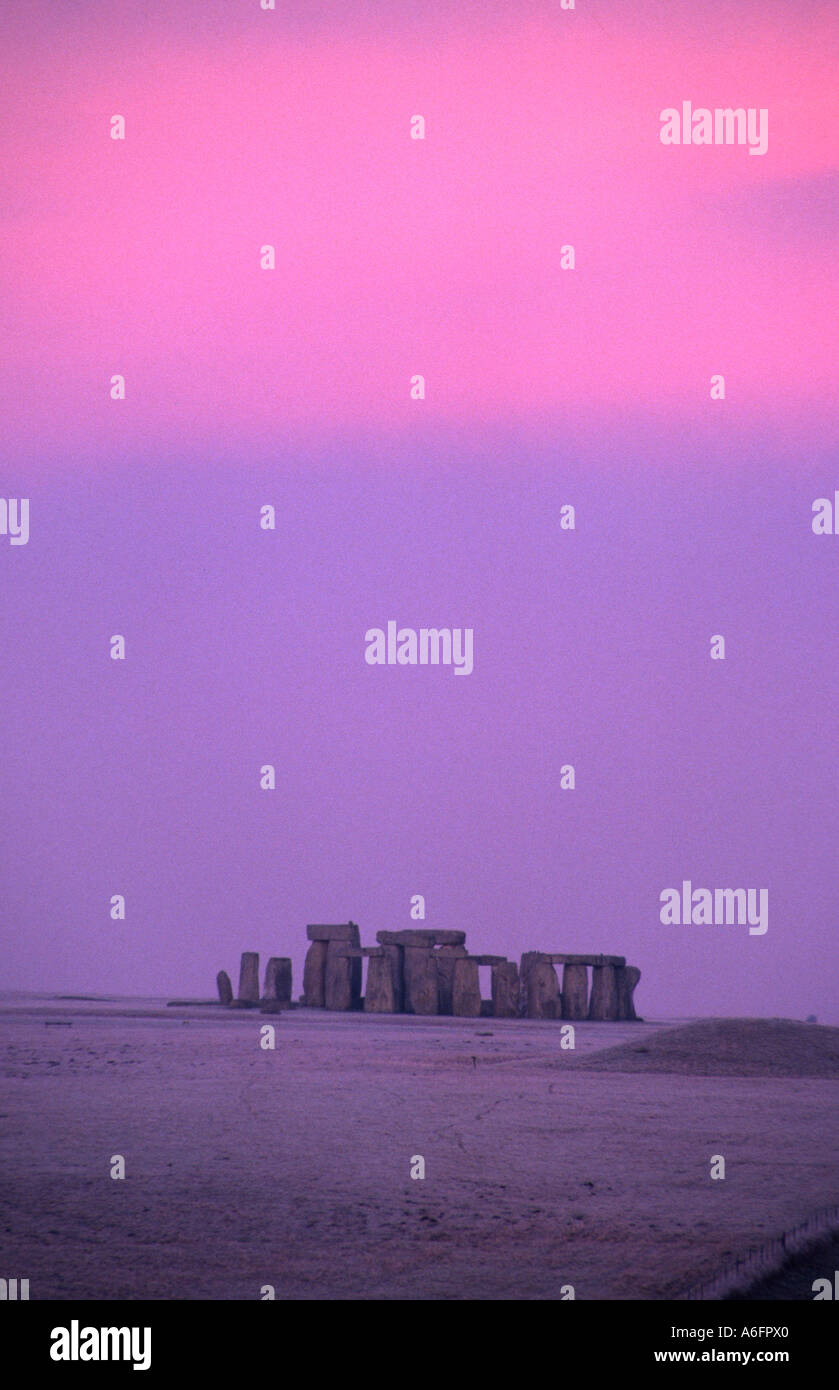 Stonehenge neolithic ancient monument site in snow against purple sunset sky Wiltshire England UK Stock Photo