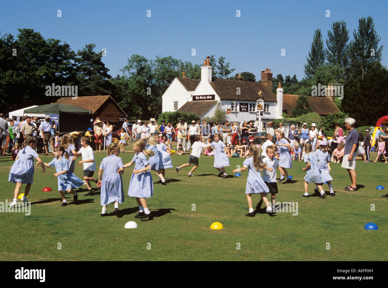 TILFORD VILLAGE SUMMER FETE with children country dancing on a village green. Tilford Surrey England UK Britain - Stock Image